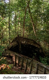 MAZIRBE, LATVIA - AUGUST 31, 2019: Stern of old, abandoned, dilapidated boat with remnants of other boats' hull laying next to it in Mazirbe Boat Cemetary, which was created in 1960s.