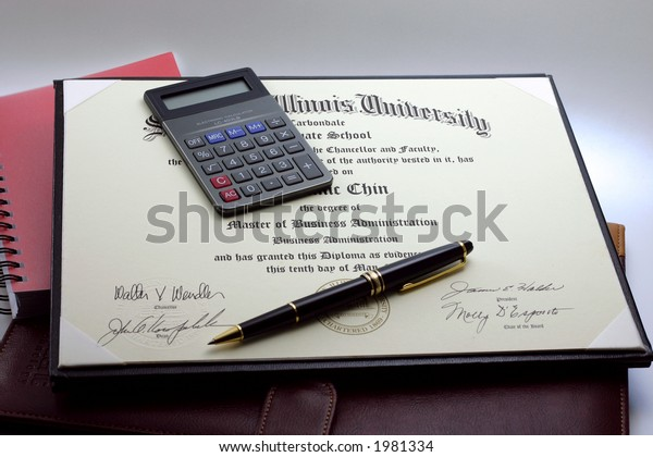 An MBA certificate with a pocket calculator and a pen lying on top; and a dark brown leather executive folder and a red ring-bound notebook underneath.