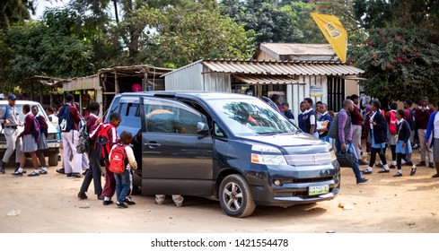 Mbabane, Swaziland, 26th May - 2019: Kids climbing into car along roadside. These cars form a network of transport getting kids to school.