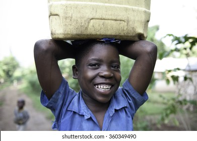 MBALE, UGANDA - NOVEMBER 15, 2013: A young girl is carrying water in Nabugoye Hill, a rural area close to Mbale.