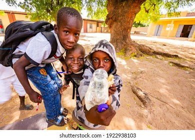 MBOUR, SENEGAL - DECEMBER Circa, 2020. Group of unidentified teenagers standing up in playground of the school , outdoors on a sunny summer day. Happy to get new bags given by international ngo.