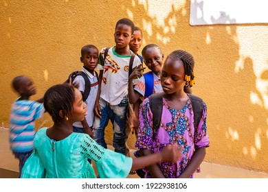 MBOUR, SENEGAL - DECEMBER Circa, 2020. Group of unidentified teenagers standing up in playground of the school , outdoors on a sunny summer day. Waiting for new bags given by international ngo.