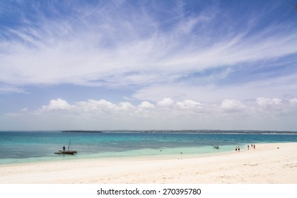 MBUDYA ISLAND, TANZANIA: MARCH 08, 2015: Local people and tourists on the beach on Mbudya Island in Tanzania, Africa, close to Dar es Salaam. Dhow boat on the left, landscape orientation, panoramic.