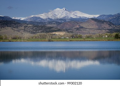 McCall Reservoir is in Boulder County, Colorado the Hygiene Area. A beautiful clear blue sky day with with low clouds and a reflection of the Twin Peaks Mt Meeker  and Longs Peak.