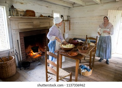 MCCONNELLS, SC (USA) - July 14, 2018:  Reenactors in Colonial period costumes demonstrate 18th Century cooking practices at Historic Brattonsville, a living history museum.