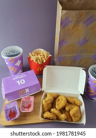 McDonalds BTS meal set. Purple background. BTS is a popular South Korea Boy band group. Meal set consist of nuggets, fries, dipping sauce and drink. Paper bag and wooden tray. Malaysia. May 2021