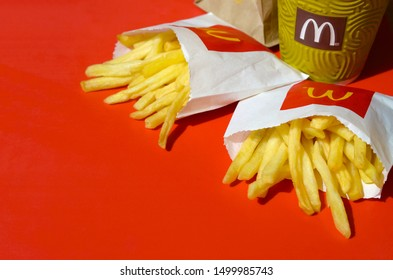 McDonald's French fries in small paperbag and coffee cup on bright red background