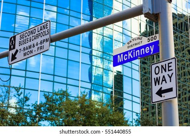 McKinney street sign in downtown Houston, Texas with a modern skyscraper in the background.