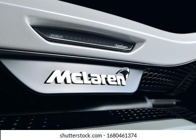 Mclaren GT rear emblem shot on a white car against a dark background, shot under studio lighting.