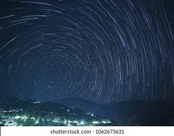 McLeod Ganj at night with star trails in sky above mountains, India