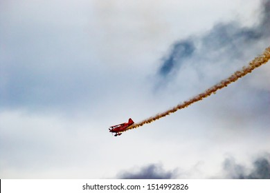 McMinnvile, Oregon - 8/21/2011: An aerobatic red biplane aircraft with smoke trail performing at the air show in McMinnvile