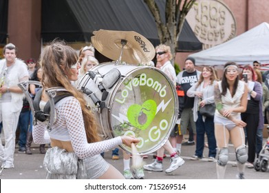 McMinnville, Oregon, USA - May 16, 2015: Portland's Marching Band, Love Bomb Go-Go, puts on a show at the Annual UFO Fest. A woman drummer plays her drum with the marching bands logo.