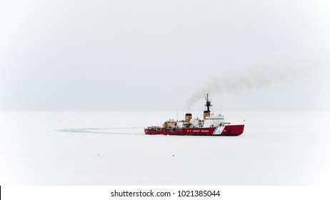 McMurdo Station, Antarctica - January 13, 2015: US Coast Guard Cutter Polar Star breaks a channel in the sea ice to provide access, for a supply vessel, to McMurdo Station, Antarctica.