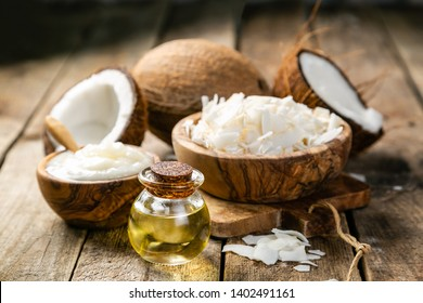 MCT coconut oil concept - coconuts, butter and oil on wood background, copy space