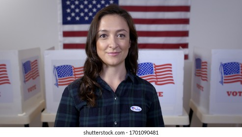 "MCU Caucasian American woman in plaid shirt wearing ""I Voted"" sticker and looking to camera, standing proud in front of polling booths with US flag"