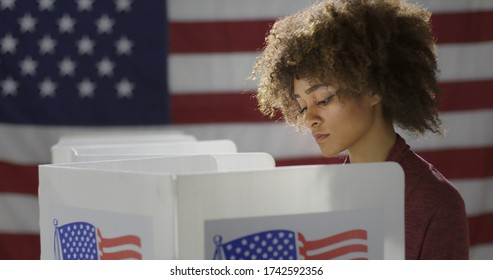 MCU profile young, mixed race woman, alone casting vote at polling station. She looks down at ballot paper, out of frame. US flag in background.