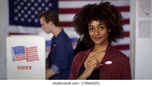 """MCU Young mixed race American woman displays """"I Voted"""" sticker while standing proud in front of polling booths with other voters, US flag at rear"""