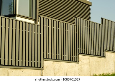 mdense opaque metal fence near the house on the slope
