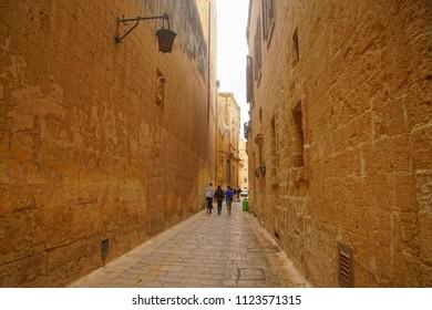 MDINA, MALTA- APR 19, 2018 - Narrow street with high limestone walls in Mdina, Malta