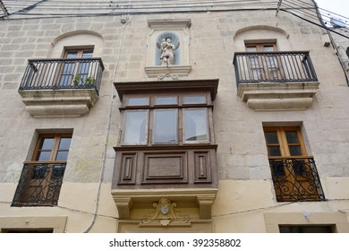 MDINA, MALTA - FEBRUARY 2, 2016. Residential building in Mdina, Malta with four ironwork balconies with brown wooden doors, a big wooden covered balcony and a religious statue of a saint on top.