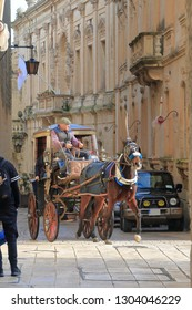 MDINA, MALTA - JANUARY 16, 2019. A horse-drawn carriage driven by an experienced coachman rolls down the streets of the ancient city.