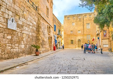 MDINA, MALTA - JUNE 14, 2018: The Mdina rd. square with its huge medieval edifices located right after the Gates, welcomes visitors of the Citadel, on June 14 in Mdina.
