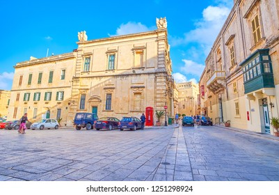 MDINA, MALTA - JUNE 14, 2018: The urban scene on St Paul Square with old medieval edifices with retro style red telephone booth, on June 14 in Mdina.