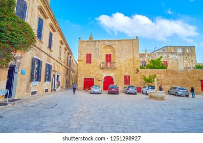 MDINA, MALTA - JUNE 14, 2018: The small St Agatha square with small stone fountain with a pillar and low edifices around, on June 14 in Mdina.