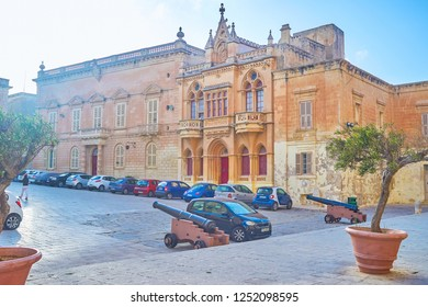 MDINA, MALTA - JUNE 14, 2018: The St Paul Square is one of the central places of the town with beautiful edifices and two medieval cannons, on June 14 in Mdina.