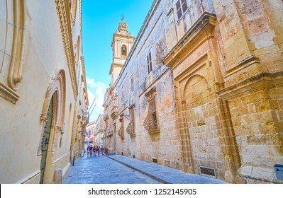 MDINA, MALTA - JUNE 14, 2018: The high walls of medieval edifices of the fortress and the bell tower of Annunciation Church, on June 14 in Mdina.