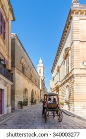MDINA, MALTA - NOVEMBER 11, 2015: Tourists being toured by horse carriage around the old city streets of Mdina, Malta on November 11, 2015.