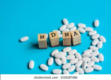 'MDMA' (Ecstasy) with wooden letters, surrounded by white pills on blue background