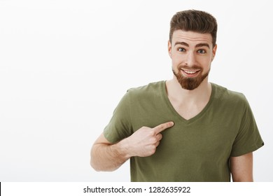 Me really you serious. Surprised happy and delighted male coworker being picked for promotion pointing at himself holding index finger directed at chest asking question at camera with joyful smile
