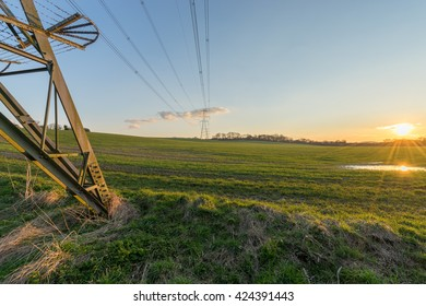Meadow and Electricity Pylon - UK standard overhead power line transmission tower at sunset