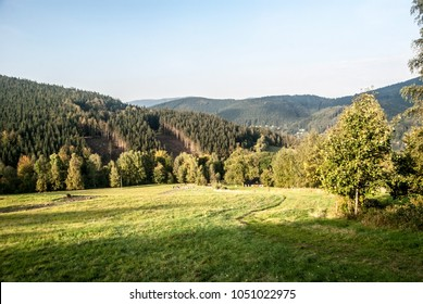 meadow with hiking trail, forest covered hills and blue sky above Krasna village in Moravskoslezske Beskydy mountains in Czech republic during nice autumn day