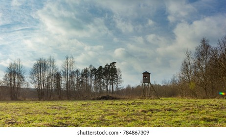 Meadow landscape with raised hide and trees under beautiful cloudy sky.