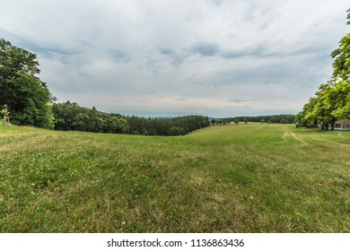 Meadow near Buchlov castle on a cloudy summer day with forest on horizon. Wide angle shot in park Chriby, South Moravia, Czech republic, Europe
