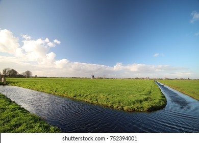 Meadow in the netherlands in Molenwaard with windwill on background and wilt blue sky en big clouds/