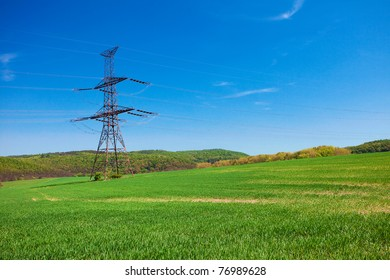meadow and power line against the blue sky