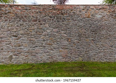 Meadow with very high old wall made of field stones