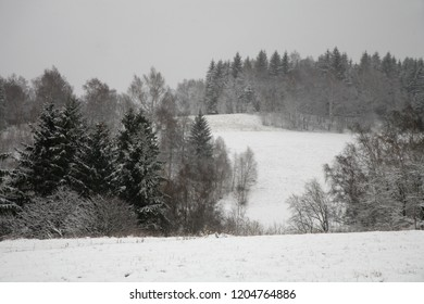 Meadows and forests covered with snow in the Stołowe, Table Mountains, National Park in Poland. Cloudy beginning of winter. First snow.