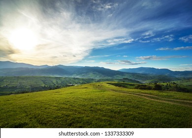 Meadows with horses, a village and a view of the mountains (Ukrainian Carpathians). Sunset landscape with beautiful clouds