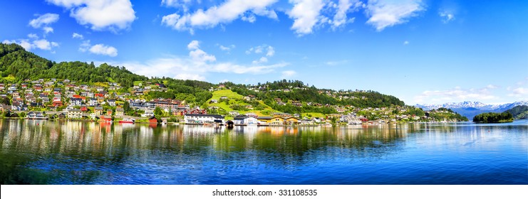 Meadows and village on Hardanger Fiord. Norway shore with view. Hardanger Fiord. Norway.