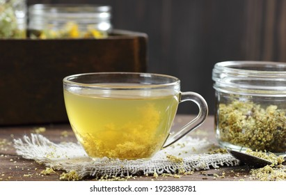 Meadowsweet floral herbal tea in glass cup on vintage books with dried herb in a jar nearby on the wooden rustic table, closeup, copy space, natural medicine and healthy herbal tea concept