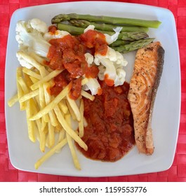 meal of fried salmon steak, steamed cauliflower and asparagus, french fries and rataouille