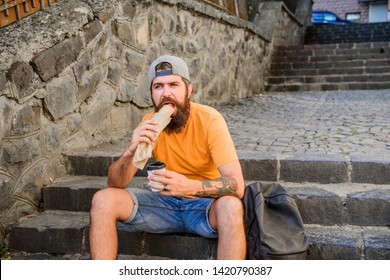 Meal just tastes better out. Hipster eating hot dog meal on stairs outdoor. Caucasian guy enjoy eating takeaway meal. Bearded man eating unhealthy hotdog sandwich during rest and meal break.