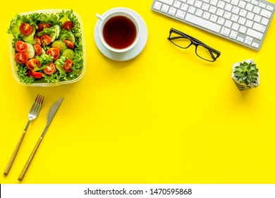 meal in lunch box and tea for dinner on yellow office desk background with keyboard top view mockup