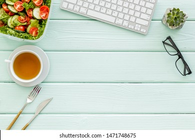 meal in lunch box and tea for dinner on mint green office desk background with keyboard top view mockup