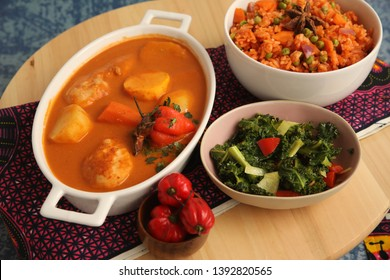 Meal on Top of Brown Table  Jollof Rice, Chicken Stew and Green Salad with Pepper on Side