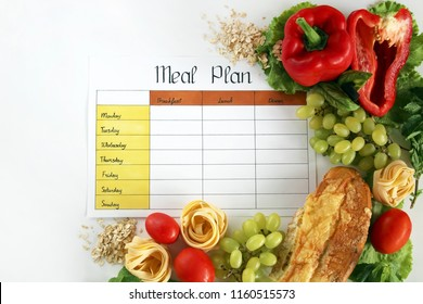 A meal plan for a week on a white table among products for cooking - pastas, basil, vegetables, cereals and spices. Concept healthy eating, dieting, slimming and weigh loss concept, top view, flat lay